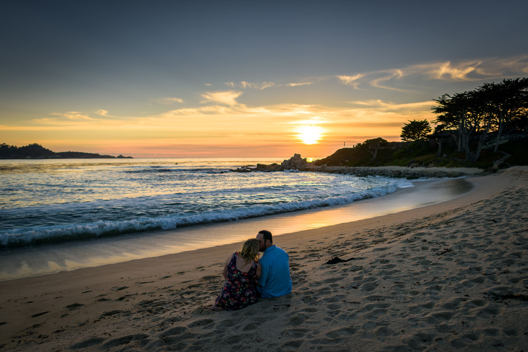couple cuddling on beach watching sunset from behind - Stewart's Cove - Carmel Engagement Photography - photos by Bay Area wedding photographer Chris Schmauch