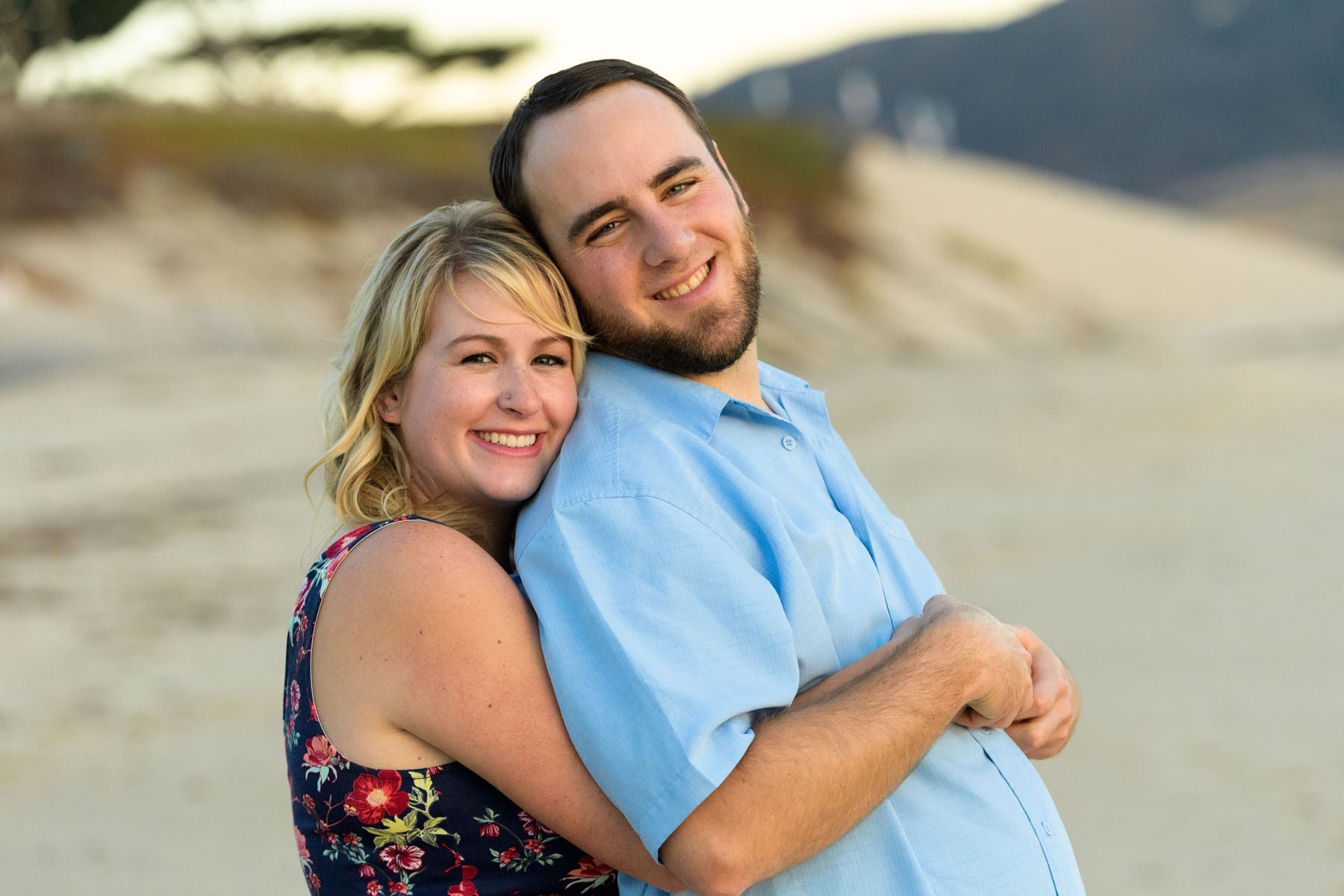 posing looking at camera cuddling on the beach at sunset - Stewart's Cove - Carmel Engagement Photography - photos by Bay Area wedding photographer Chris Schmauch