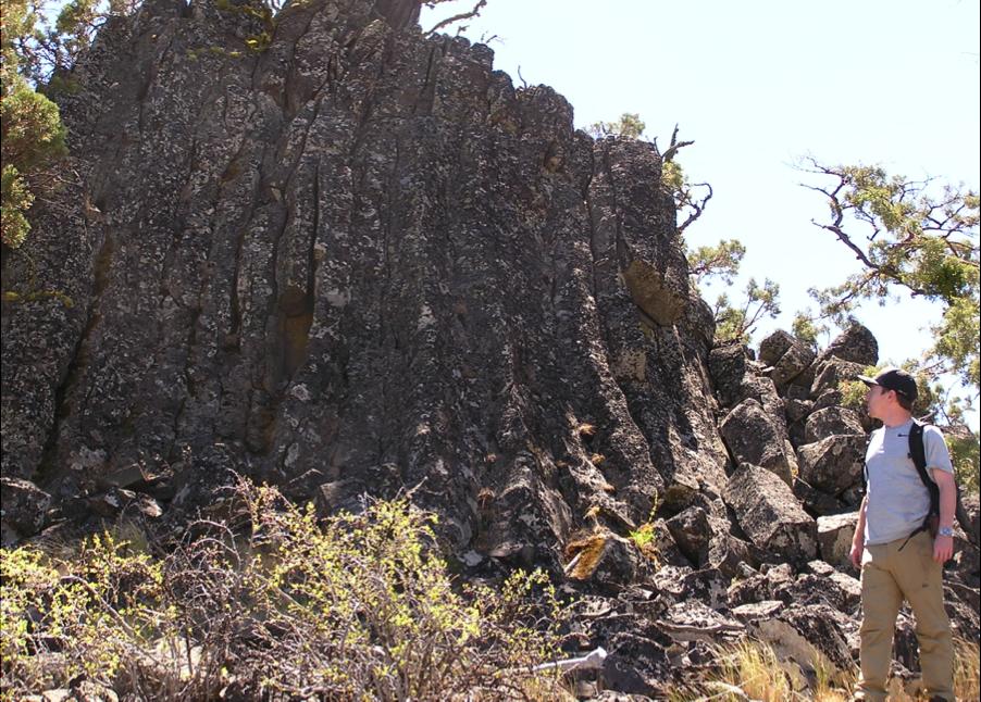 Kieran McCann stands next to a dike formation found near Mt. Rosebud. Photo by Jad D'Allura