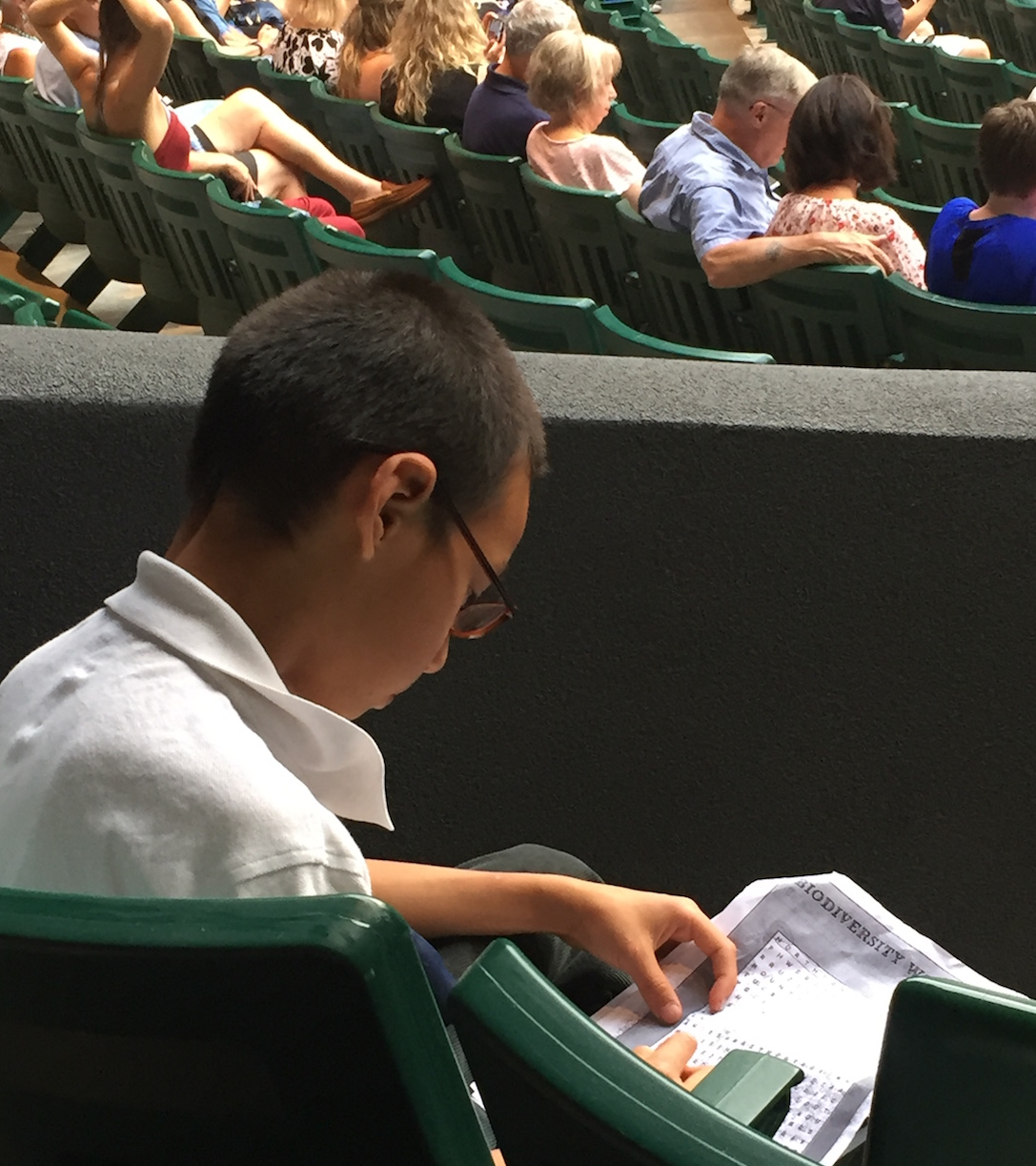 A boy works on his Junior Explorer workbook while waiting for an evening OSF performance. C Beekman photo.