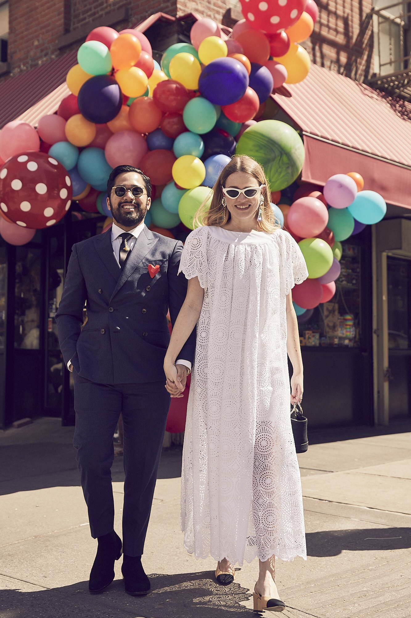 Dress,  Allison Fry . Handbag,  Simon Miller.  Shoes,  Chanel . Sunglasses,  Le Specs by Adam Selman . Earrings,  Alessandra Rich .  Bibhu wears    Suit by  J.Crew . Tie by  Gucci . Sunglasses,  Gucci . Boots,  Saint Laurent .