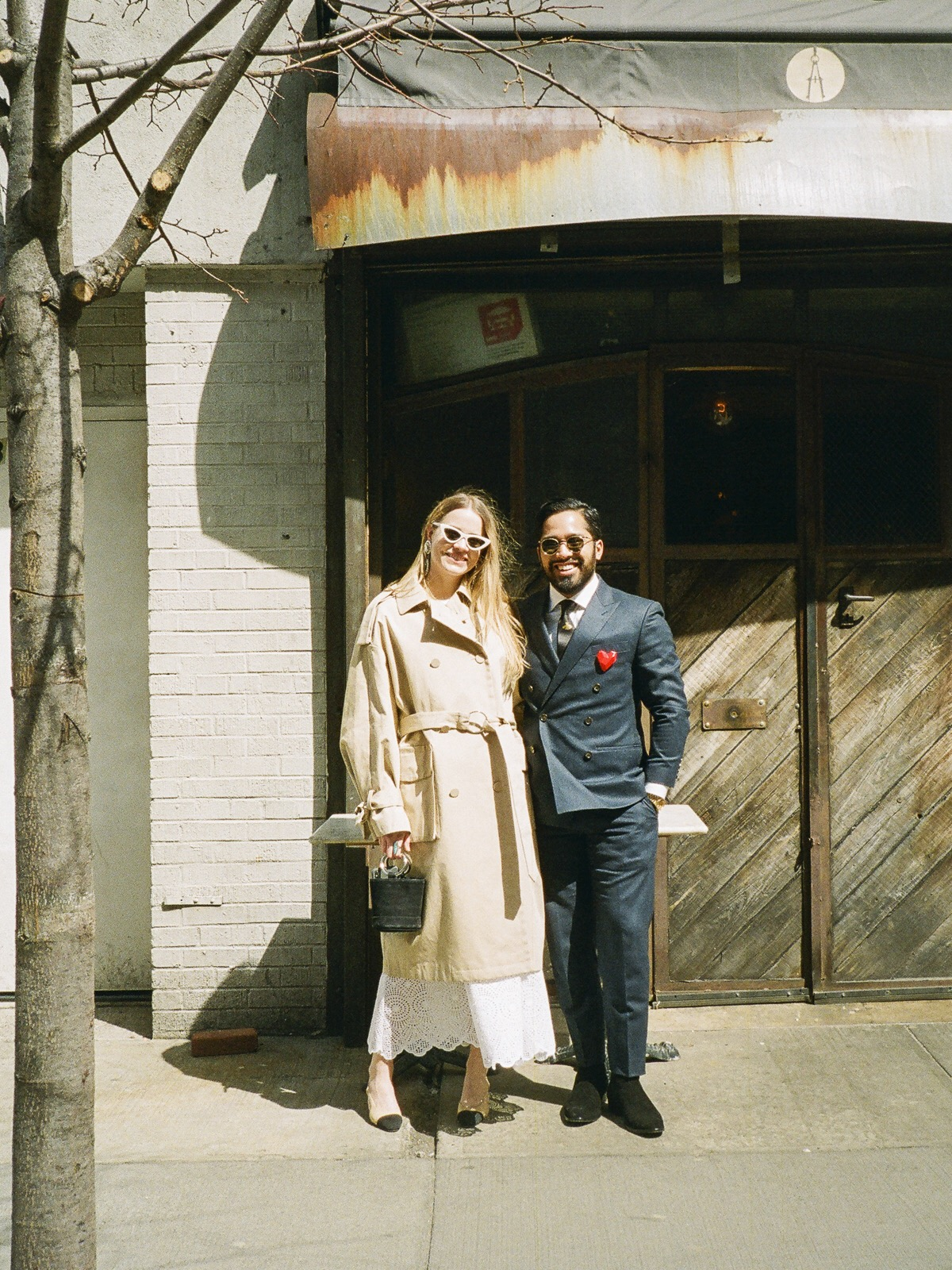 Trench,  & Other Stories . Dress,  Allison Fry . Handbag,  Simon Miller.  Shoes,  Chanel . Sunglasses,  Le Specs by Adam Selman . Earrings,  Alessandra Rich .  Bibhu wears    Suit by  J.Crew . Tie by  Gucci . Sunglasses,  Gucci . Boots,  Saint Laurent .