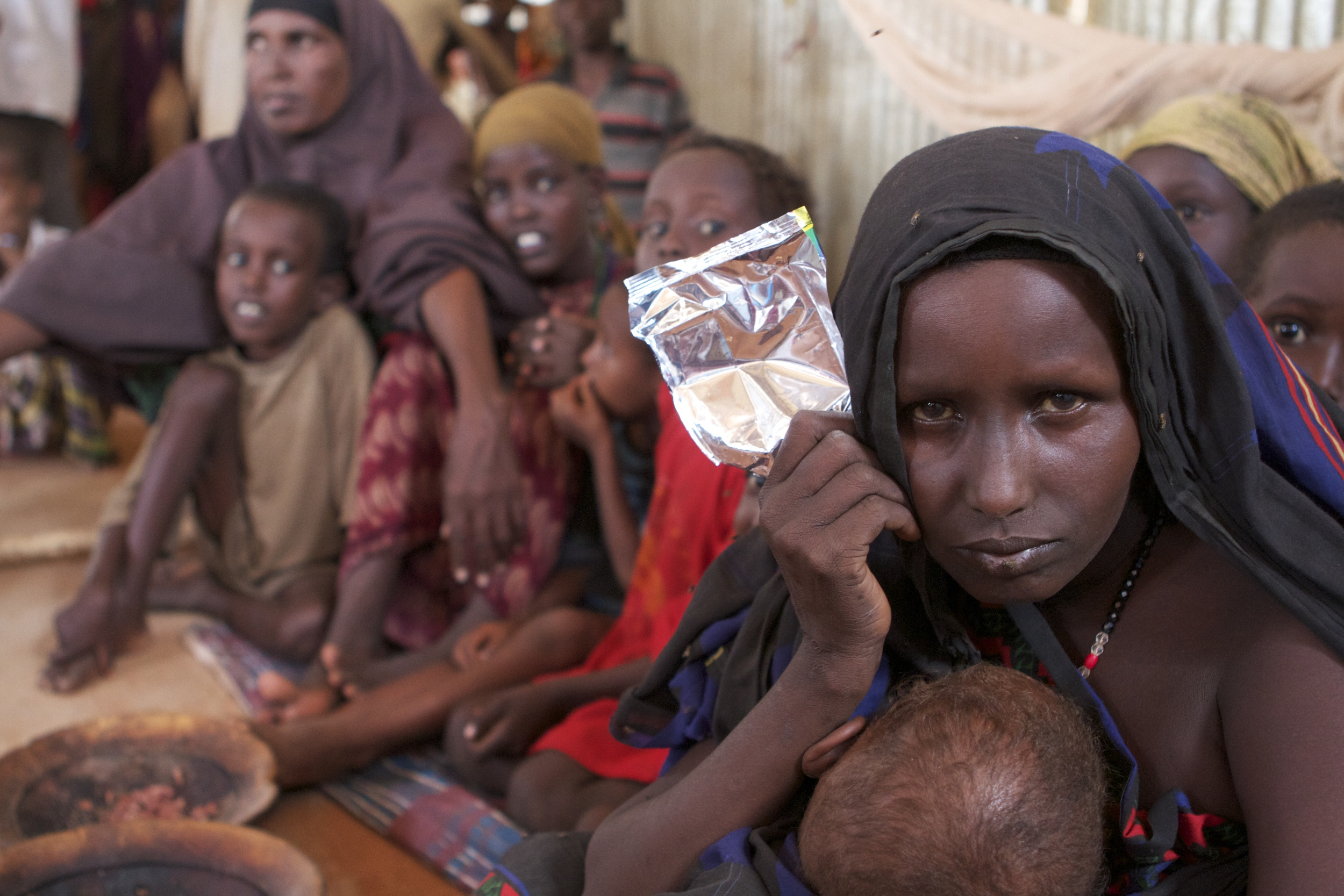 A Somali woman and her family in a communal tent in the Dolo Ado refugee camp. Her family had to walk for over 10 days to reach the camp, during the 2011 famine