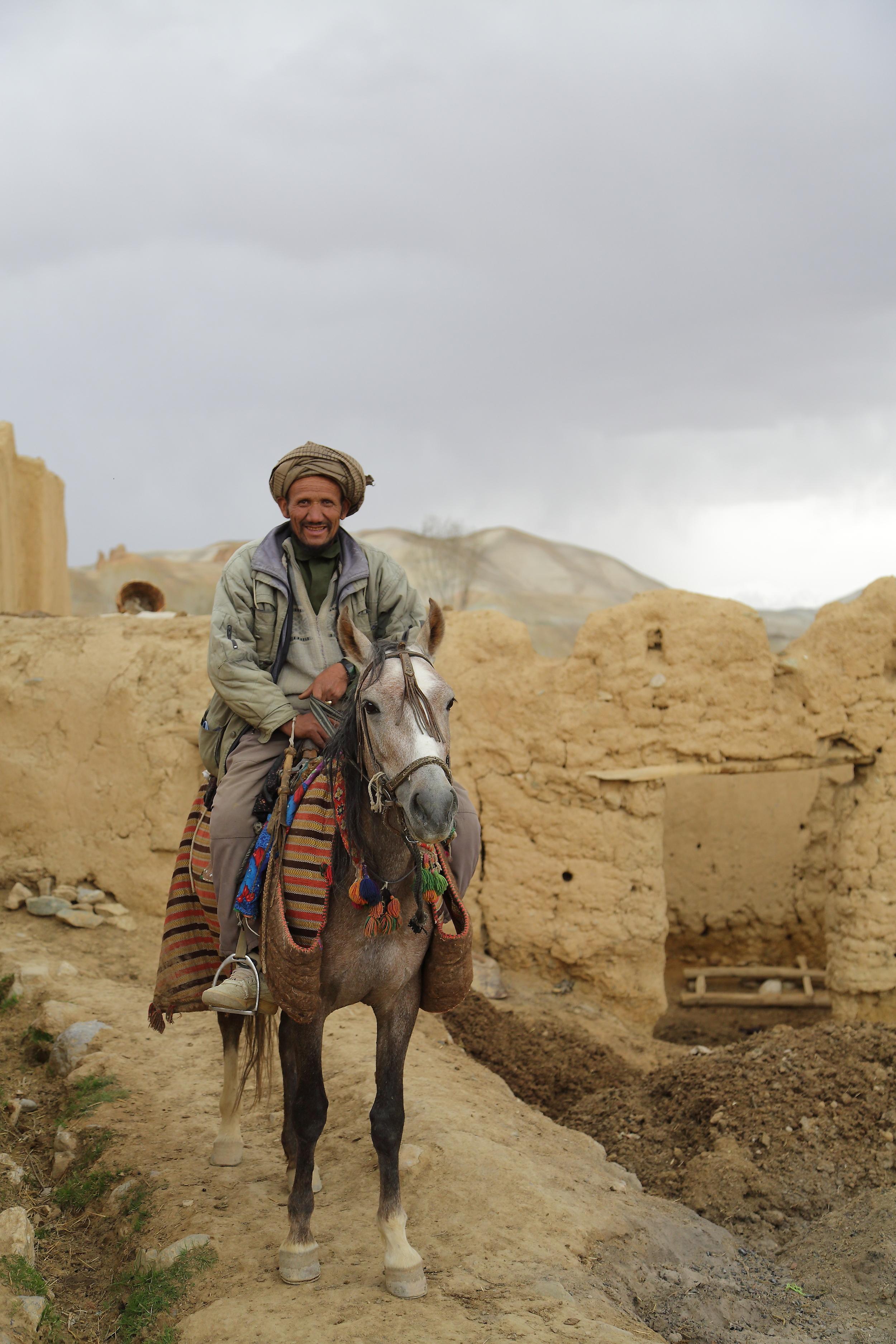 An Afghan man rides his horse through his village