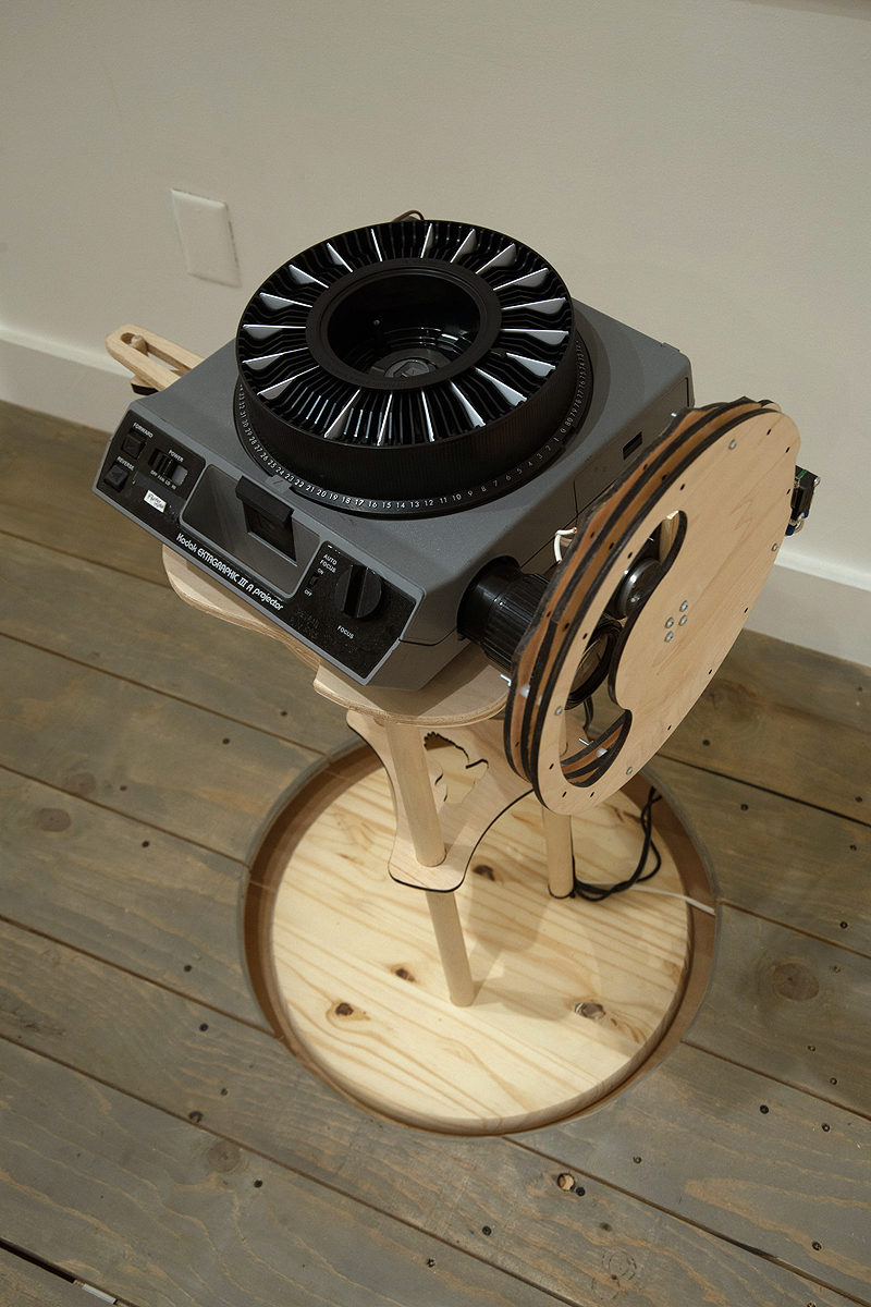 The slide projector stands are kinetic and respond to the footsteps of gallery visitors.