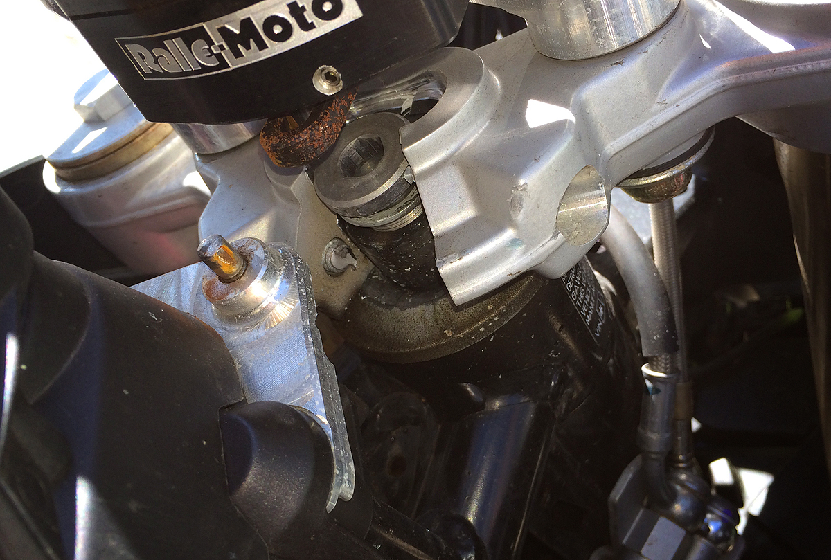 The force bent the upper section of the fork clamps shearing the bolt that secured it to the steering head.