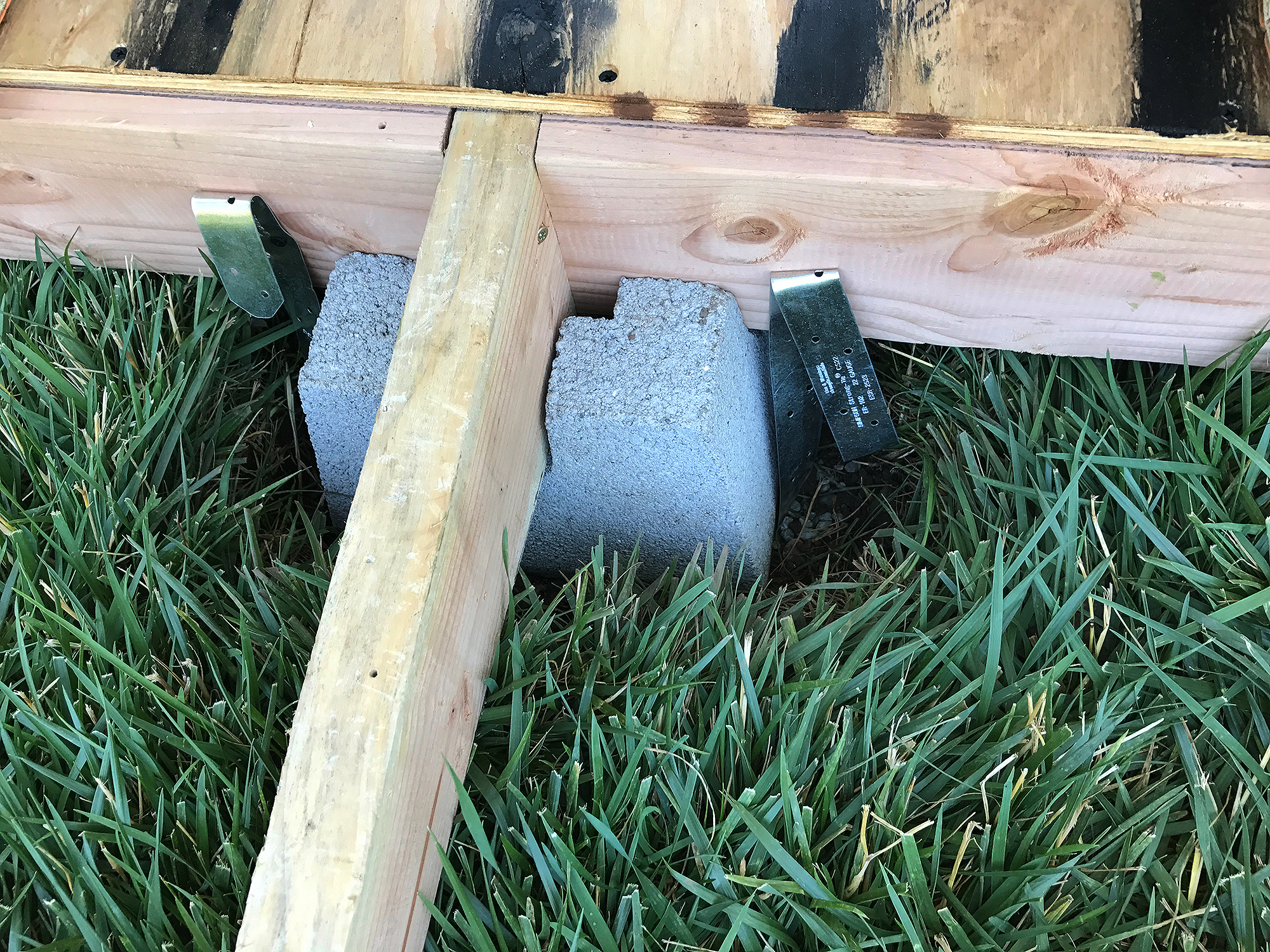 blocks are sunken into the lawn to support the frame