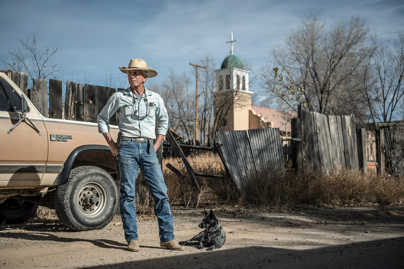 David   and his dog Perdida . During the week he works as a constructor. I asked him to pose for a while. I liked his appearance with his hat and his sweet dog. The location was perfect, the car, the church and his hat.....all in the same color. (Cerrillos, New Mexico, US)