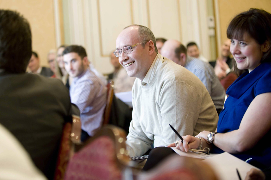Candid portrait of an attendee smiling man at an event in London