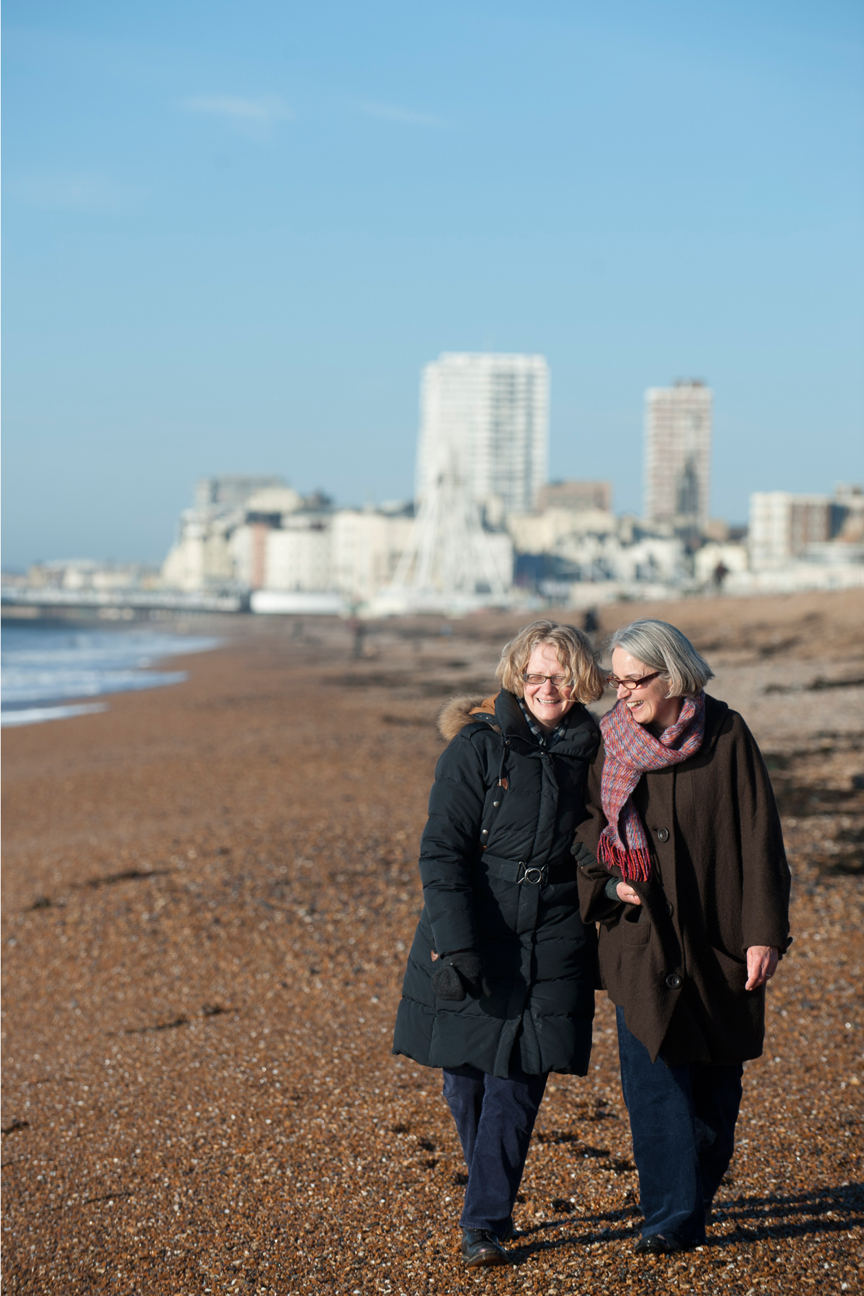 Marketing Portrait of two women walking along Brighton Beach, laughing