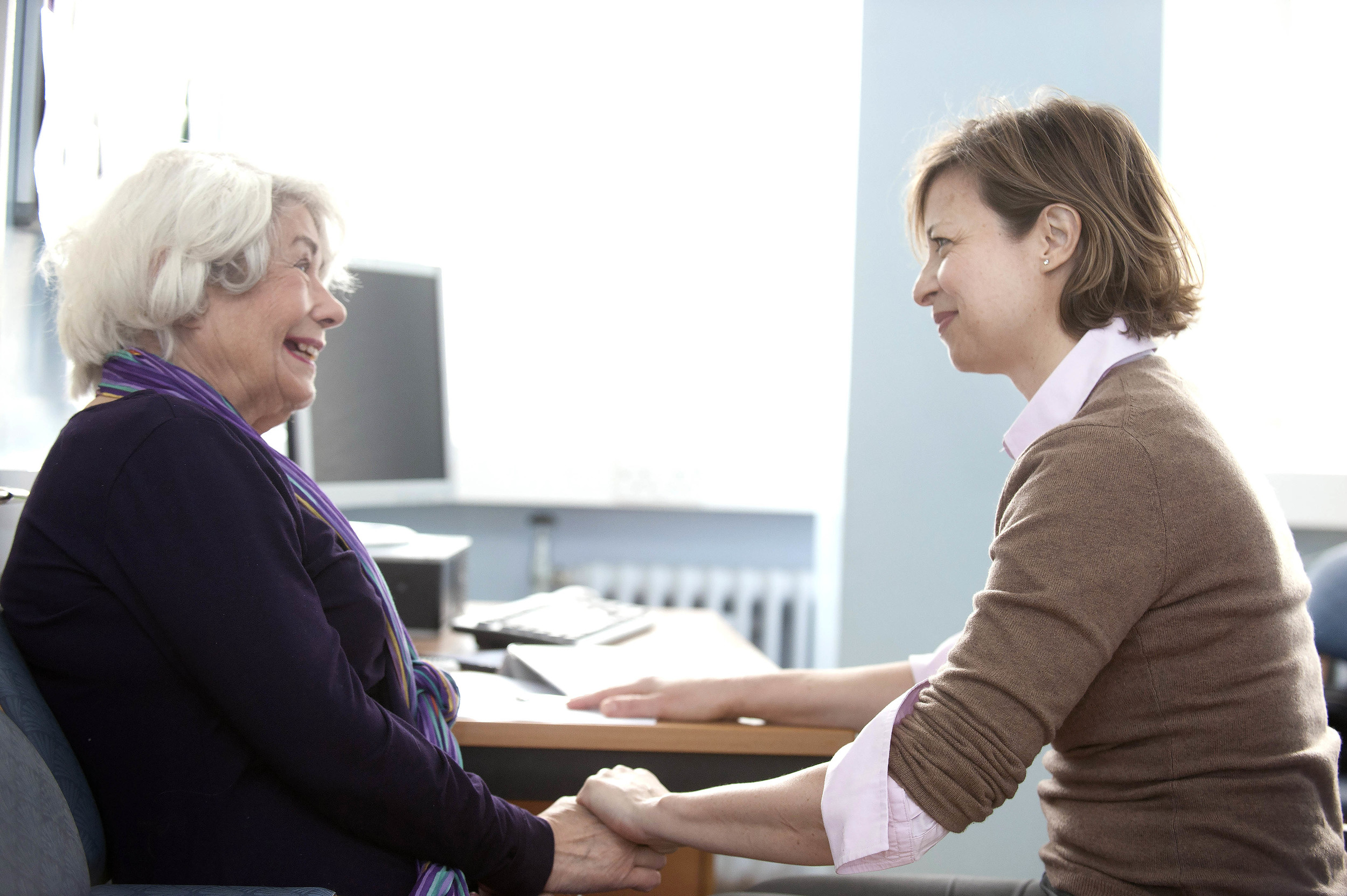 A medical professional consulting with a patient holding her hand smiling
