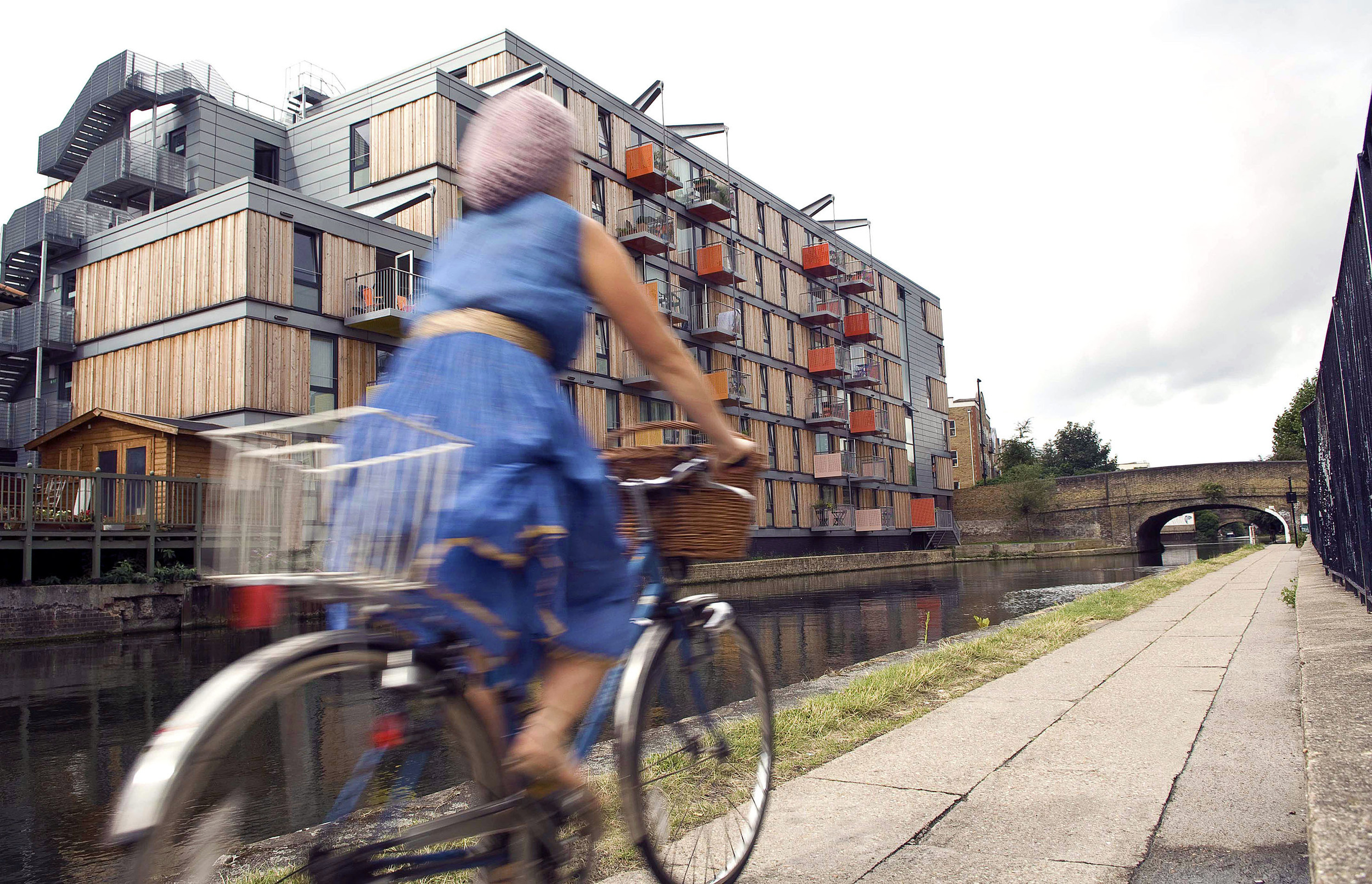 Environmental portrait of a woman on a bike cycling by a canal in London