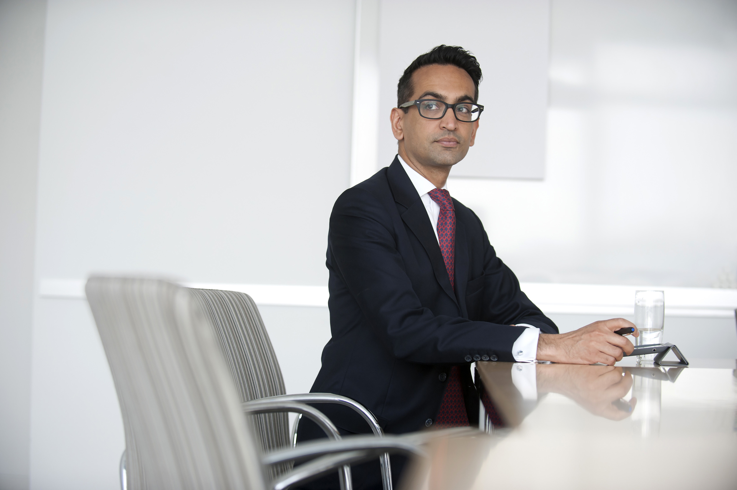 Corporate portrait of a lawyer in a suit sitting looking away from camera