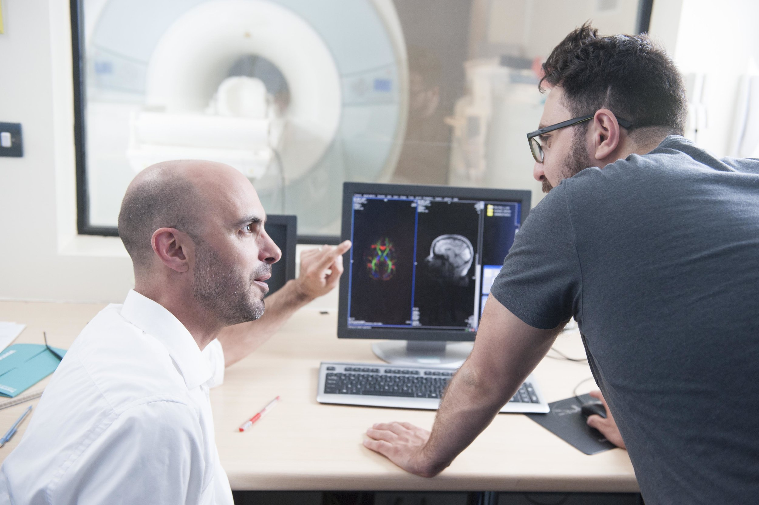two medical professionals discussing an image from a scan on screen