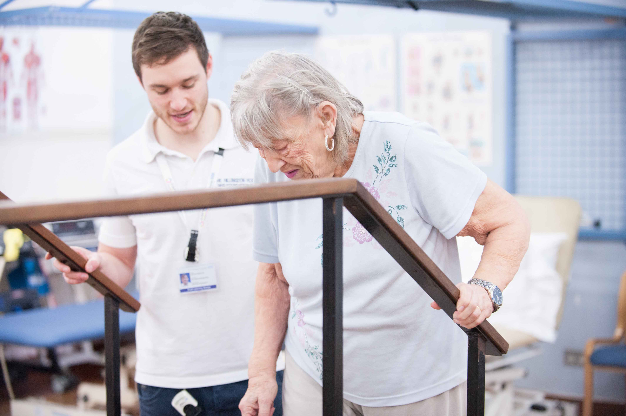 A physiotherapist helps and elderly woman to walk using walking bars in Hospital