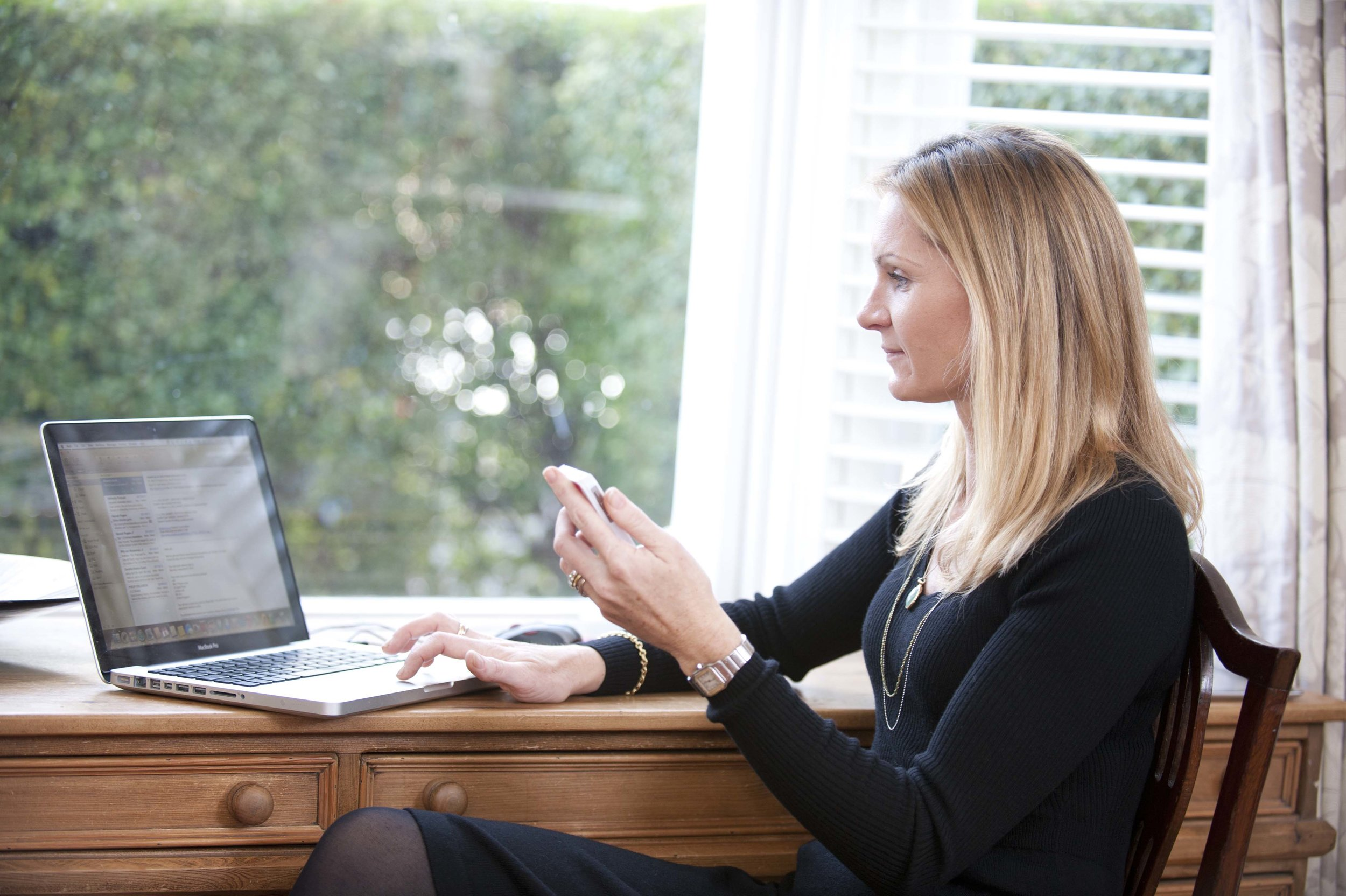 Marketing portrait of a woman using a mac and a mobile device