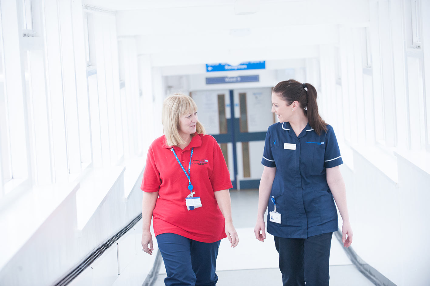 Two nurses walking down hospital corridor smiling at each other