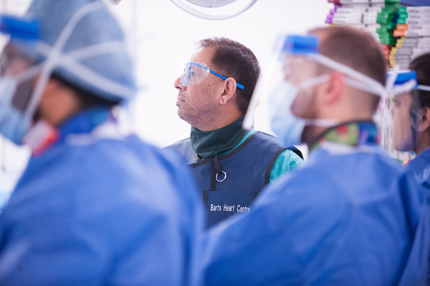 A surgeon concentrating looking towards a monitor during an operation