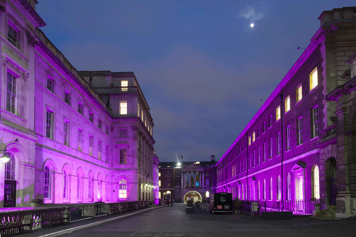 Kings College London building at night illuminated in purple