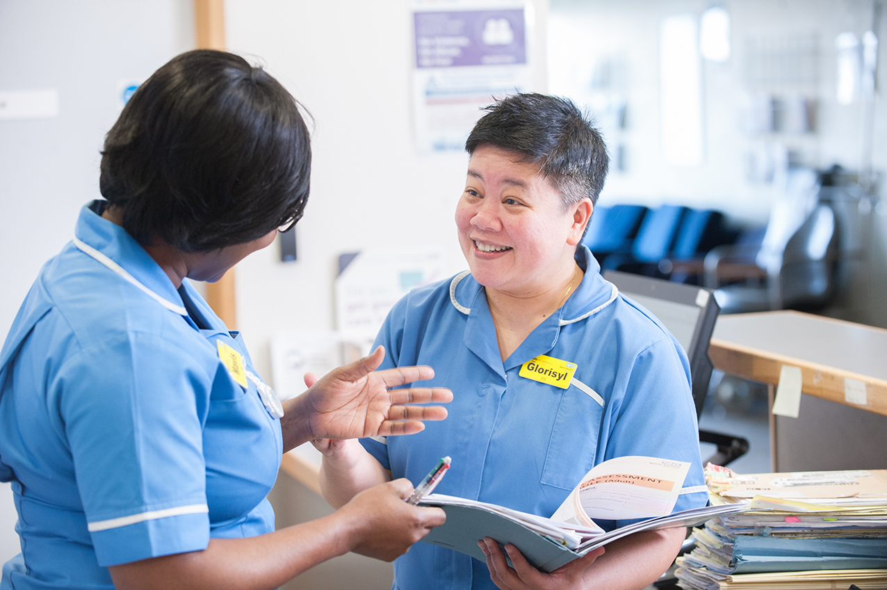 Two nurses discussing medical notes smiling in a london Hospital