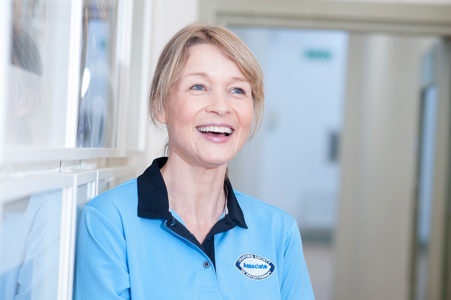 Headshot portrait of a women physiotherapist Laughing
