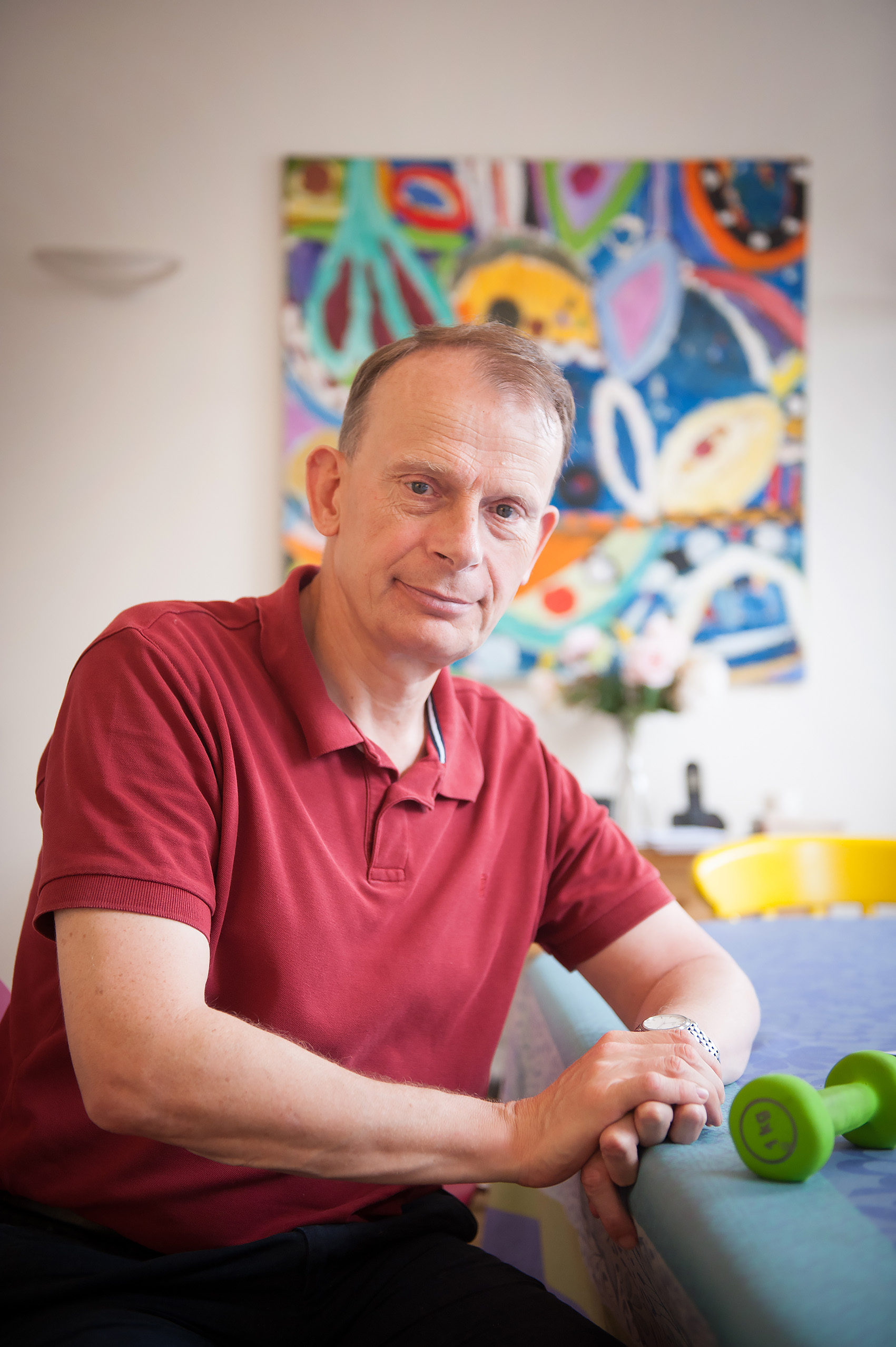 Portrait of Andrew Marr sitting in front of a abstract painting