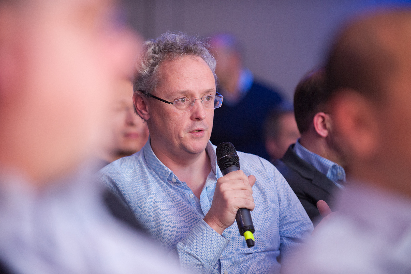 Candid portrait of an attendee speaking during a Q&A at a conference event