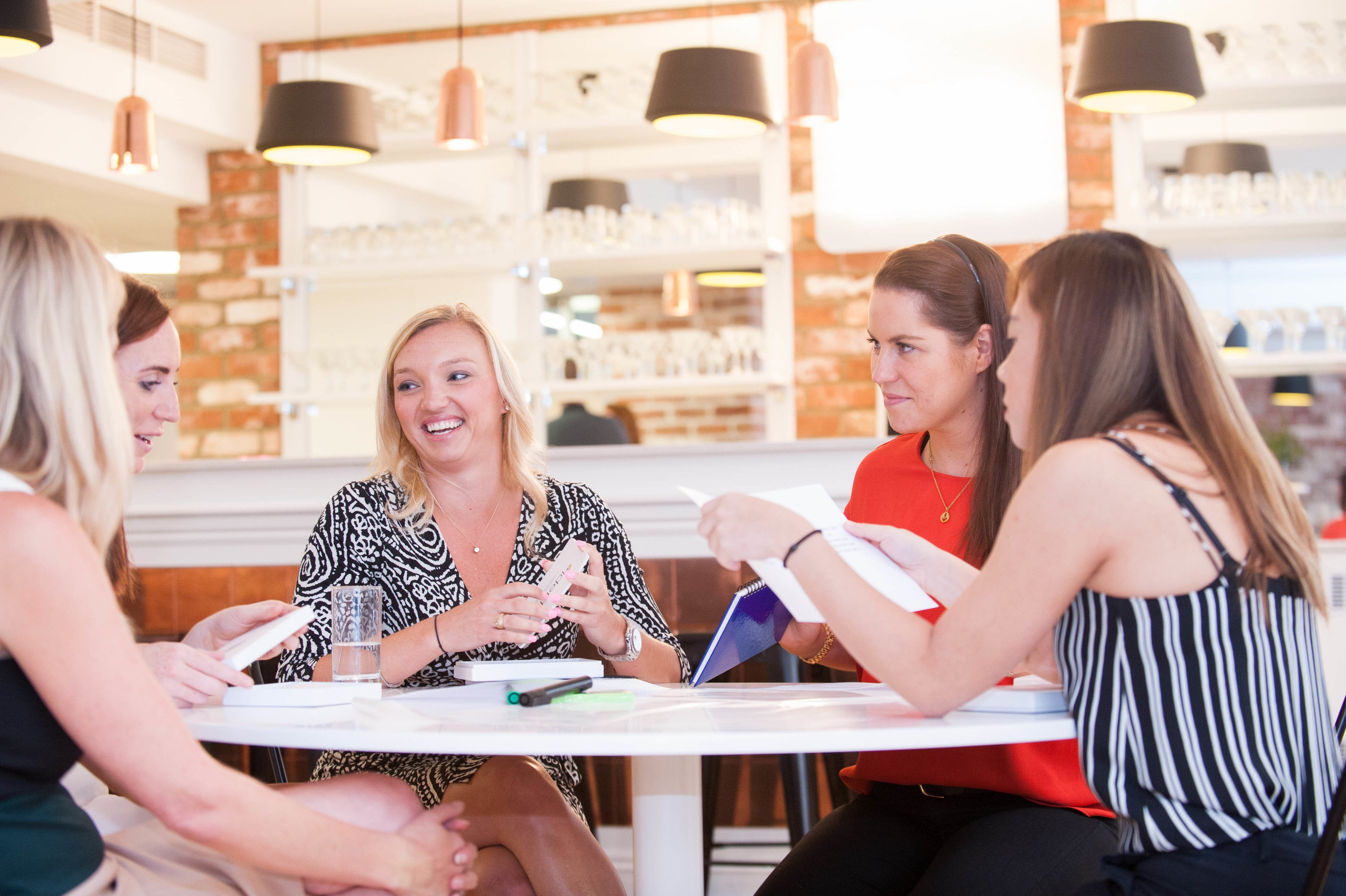 Women laughing round a table during an event workshop session