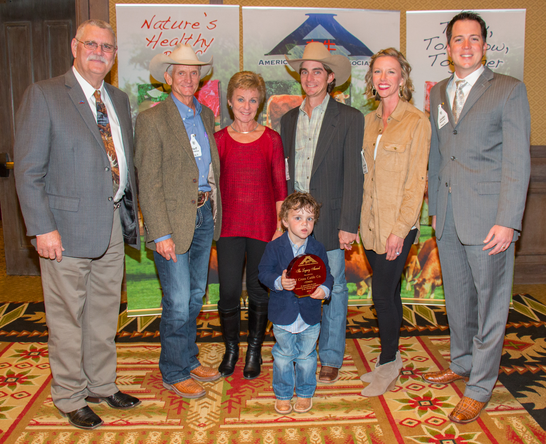 Bubba Bain, Executive Director American Akaushi Association with E Cross Cattle Company the 2015 Legacy Award Winner; Herff and Nancy Cornelius, Len and Savannah Cornelius, Jordan Beeman, President HeartBrand Beef, Inc., in front holding the award is Wyatt Cornelius, son of Len and Savannah.