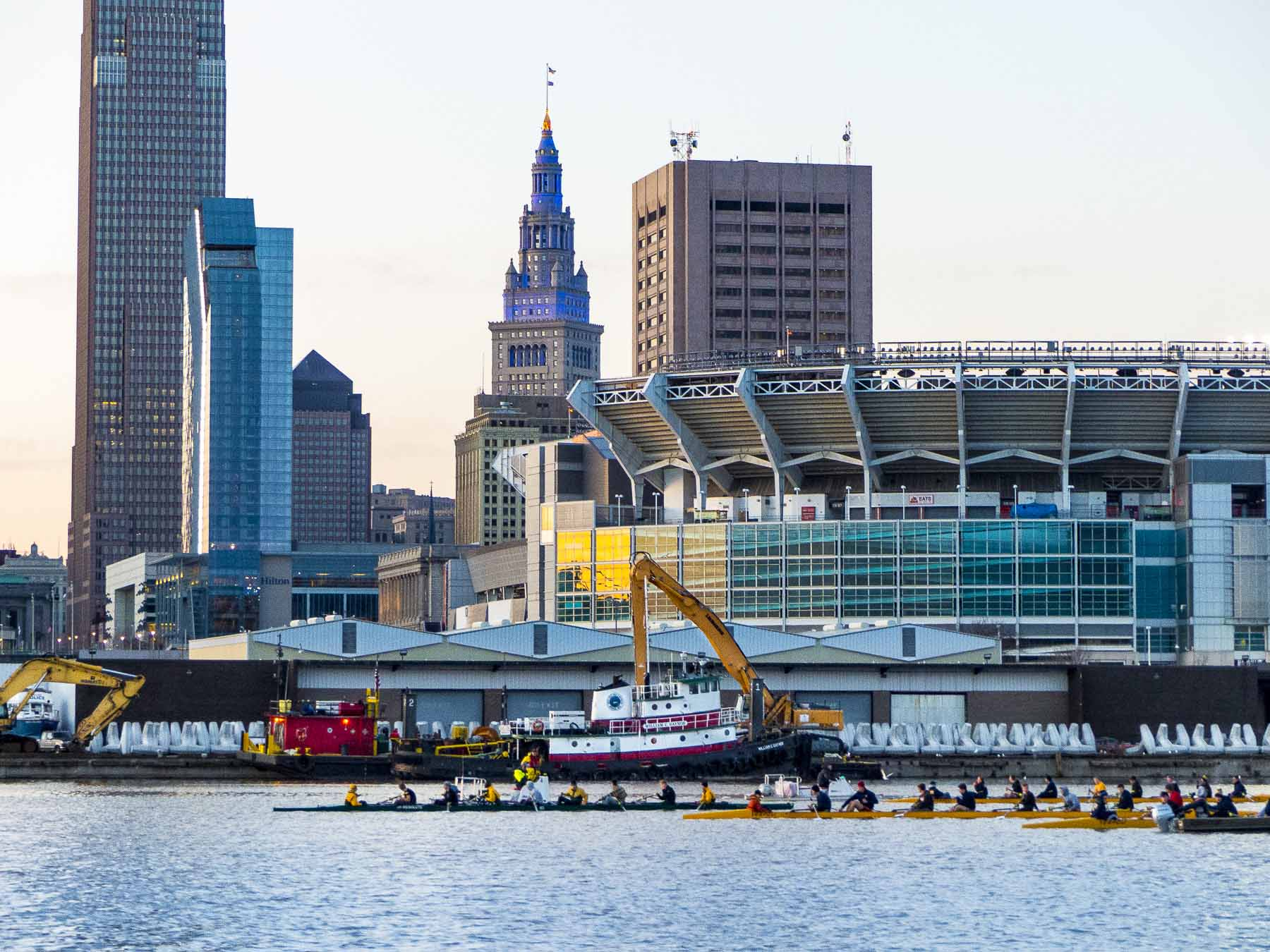Rowing shells line up in front of Port of Cleveland docks where dolos await transport to the U.S. Army Corps Cleveland Harbor East breakwall repair project