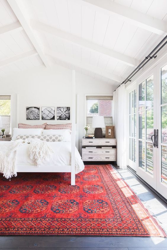 white bedroom with red rug, eclectic design