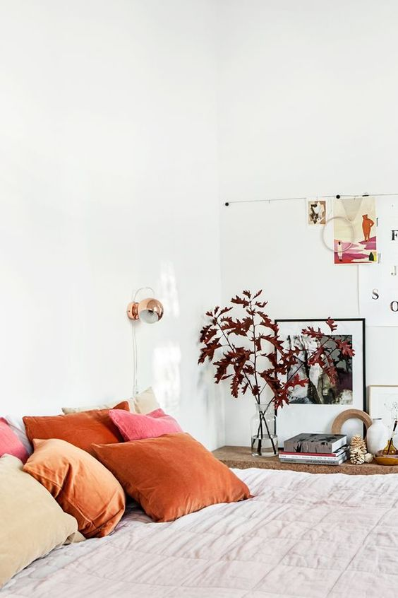 neutral bedroom with pops of red and rust