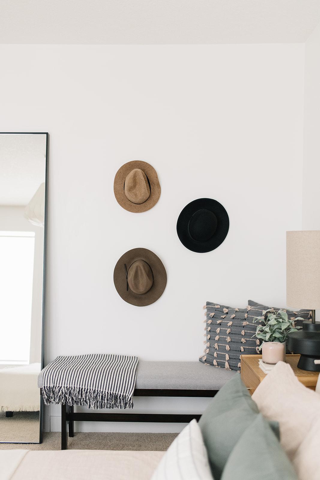 minimalist bedroom, hats on wall in bedroom