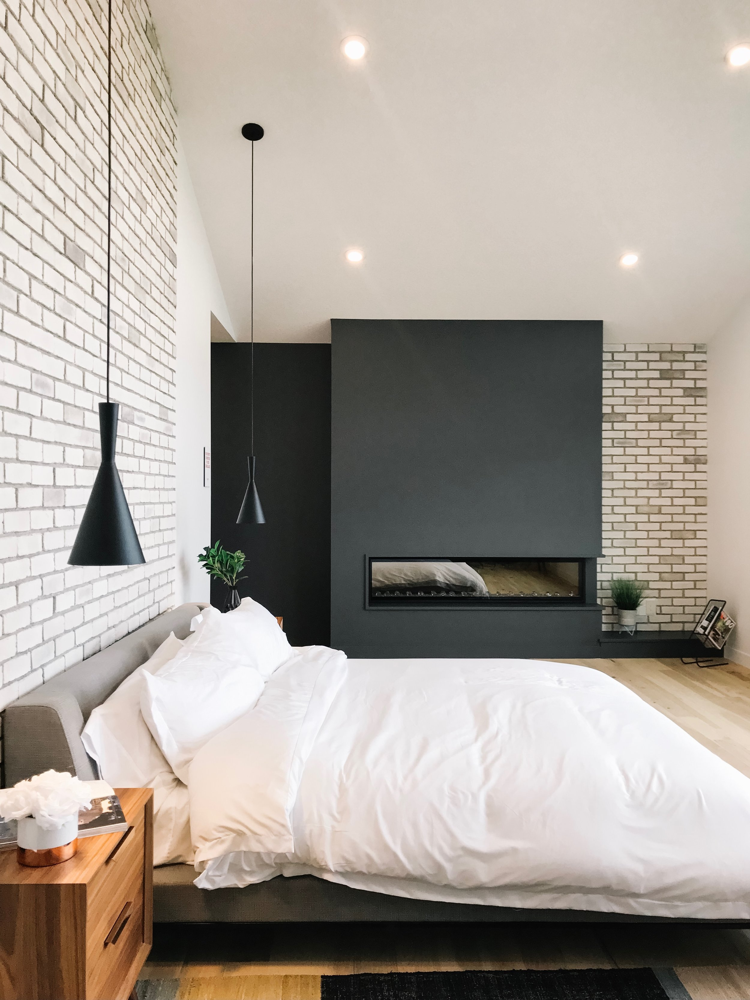 modern bedroom with brick and fireplace
