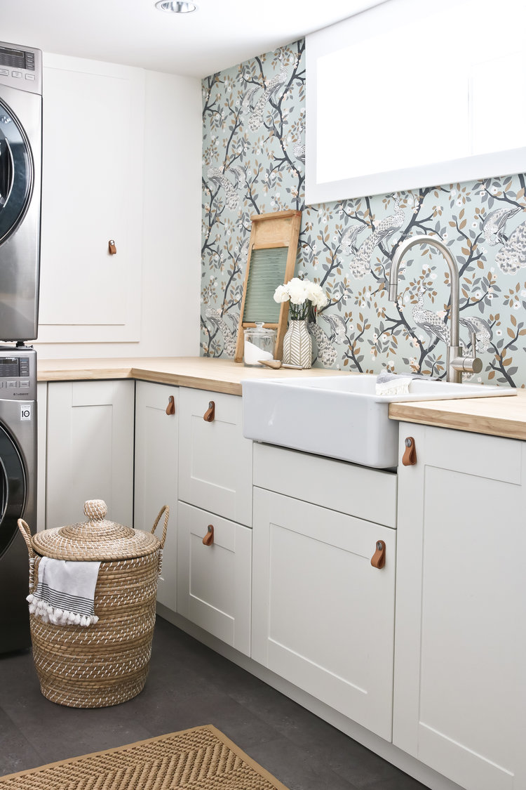 laundry room with white cabinets and wallpaper