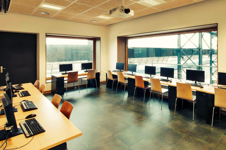 """Einer der drei Computerräume der Vaclav-Havel-Bibliothek mit Blick auf die Bahngleise. Sie ist Teil des  Projektes """"Halle Pajol"""": I n umgebauten Lagerhallen gibt es unter anderem auch ein preiswertes Hostel mit 330 Betten, ein Café, ein Atelier mit 3D-Druckern, ein Gymnasium, eine Sporthalle und einen Wintergarten.   Link zum Blog der Bibliothek"""