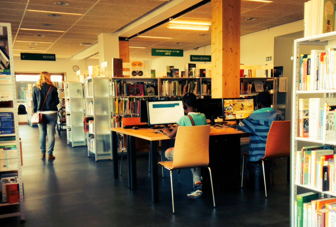 Zwischen den Bücherregalen warten Computer auf die Besucher..
