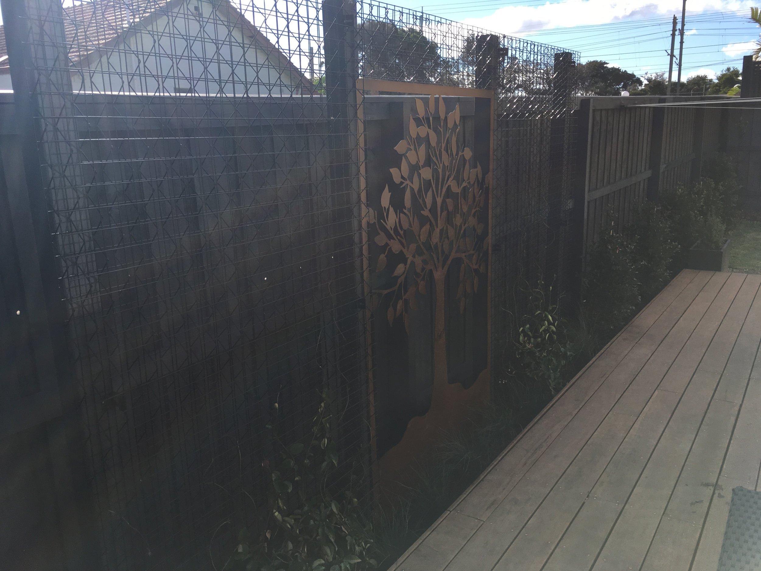 Seaford Courtyard/Garden. Entanglements Feature Screen. Archbar 3D Trellis. Syzygium australe, Lomandra 'Seascape'. Trachelospermum jasminoides 'Star Jasmine'. Merbau Decking.