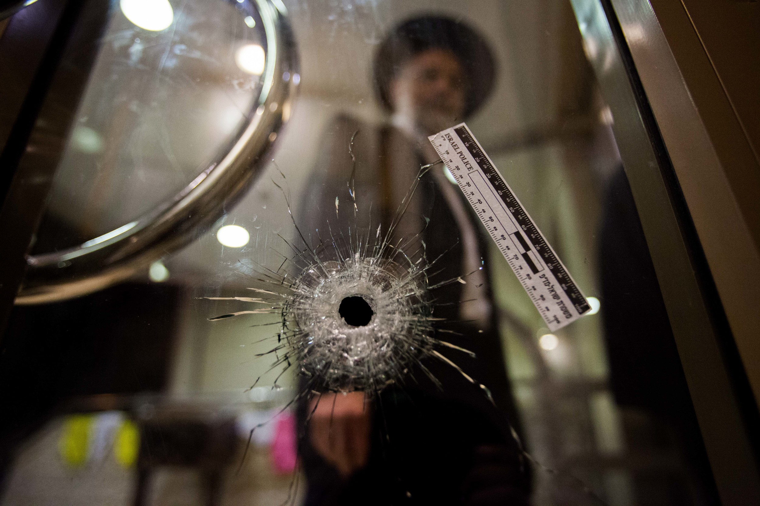 A man walks next to a bullet hole inside a synagogue where two terrorists Attack the Kehilat Yaakov synagogue in the Jewish orthodox neighborhood of Har NofJerusalem on November 18, 2014.