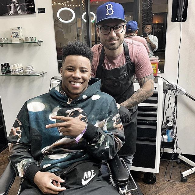 @therealbarberal wearing @knifeandflag Non Porous Apron in Black, with @saquon!!! #barber #workwear #survivalunion #knifeandflag #craftsman