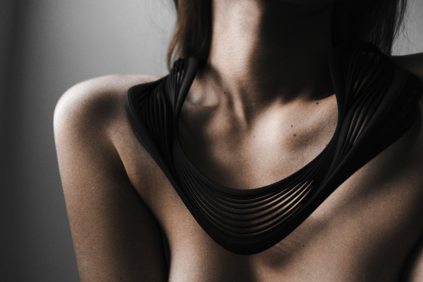 blackswan necklace, 3D printed necklace in nylon based material, photography by cate underwood  the necklace is articulated as a series of lines inflecting on one another to create a sinuous ripple effect on the female body. the blending of curves with one another create an harmonius differentiation within the various components around the neck