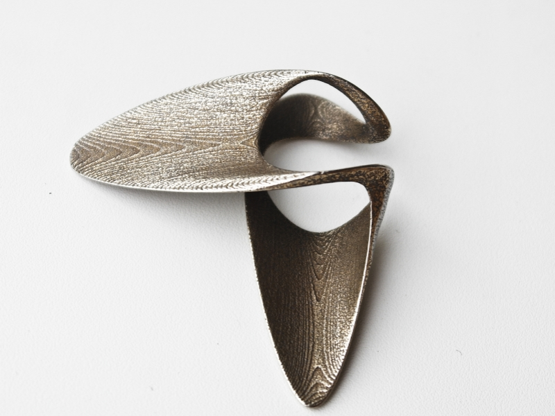 splint ring, 3D printed steel ring, photography ldvc ludovico lombardi   the design uses the different degrees of freedom and movement of the hand and fingers to generate a ornament that respond to the constrains of the specific body part. the ring is 3d printed in steel with raw finish. the metal wraps on the side of the hand looping in between the fingers in a continuous geometry symmetrical along two different axis.