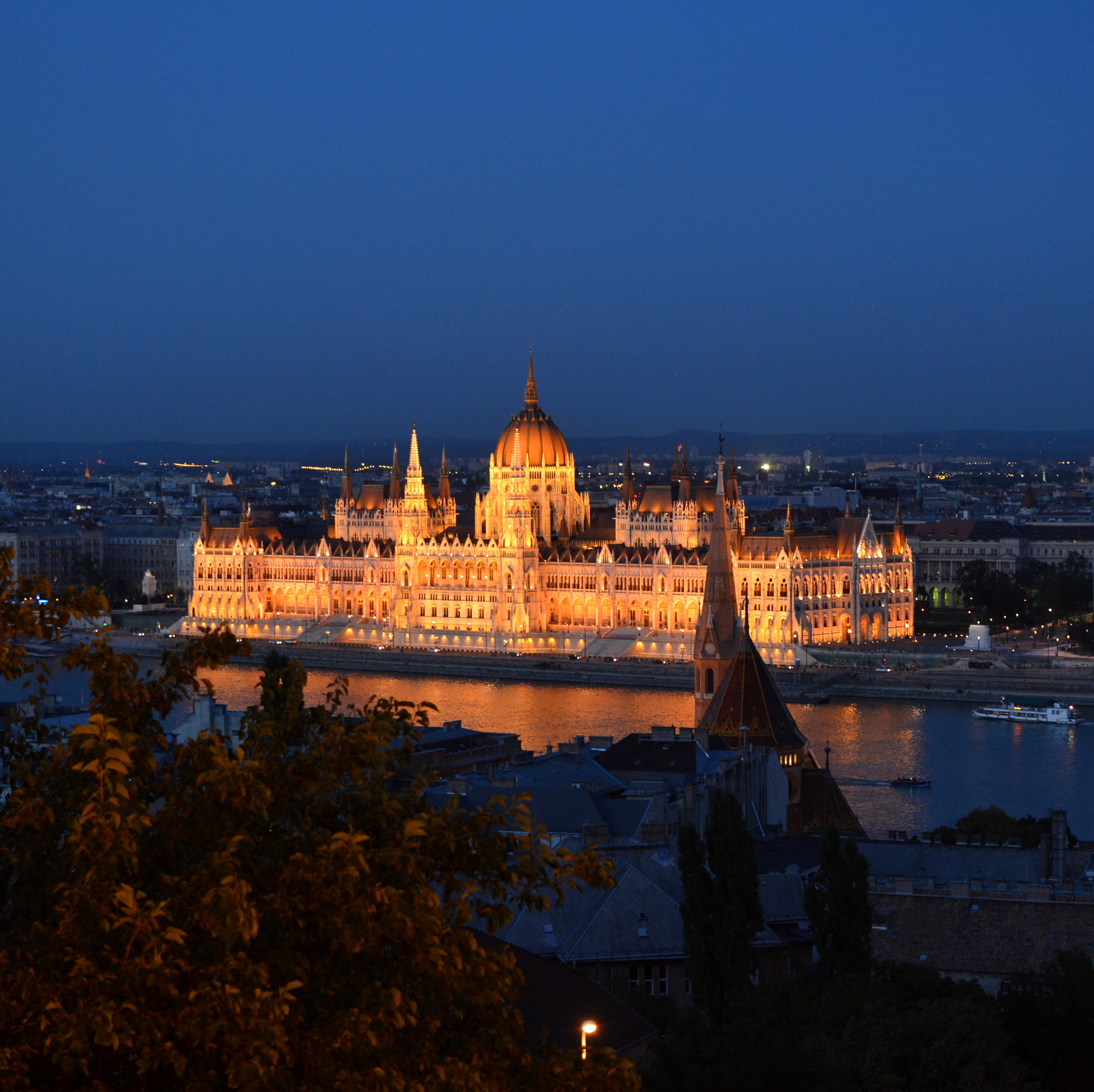 The Hungarian Parliament building lit at night along the banks of the Danube.