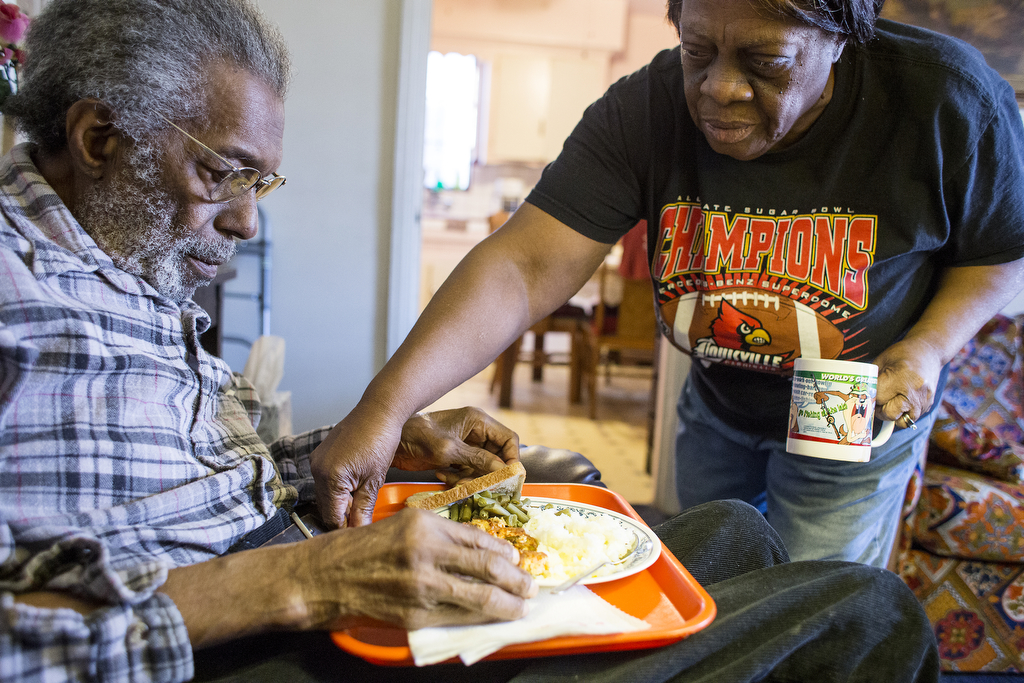 Beatrice Ford serves her husband, Hugh, a meal of part Detroit Meals on Wheels delivered food and part her own cooking in their home, April 18, 2014. She serves it to him on a red plastic tray and balances a lamp on a TV table to help him see.