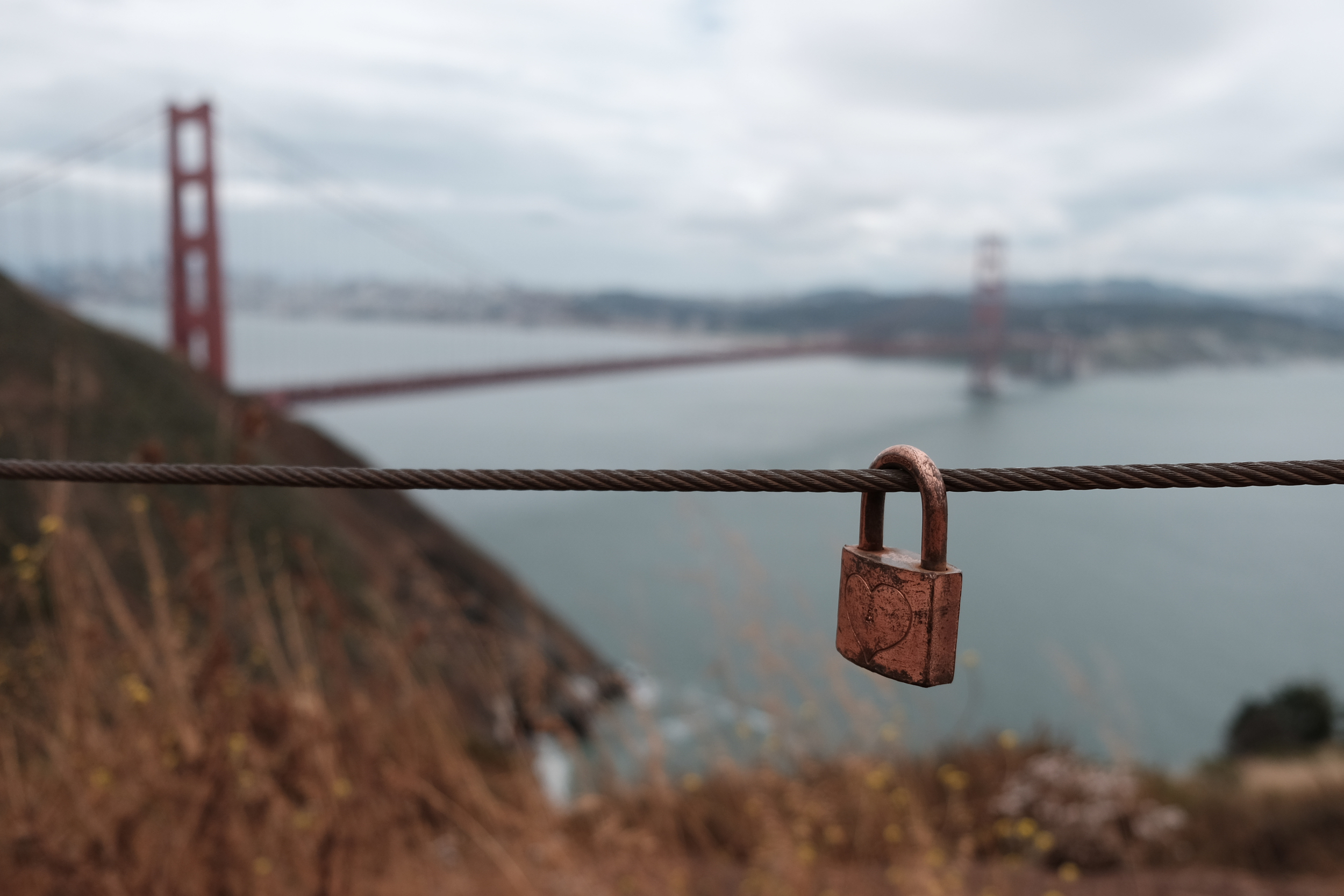 Lock attached to fence cable, located at a viewpoint above the Golden Gate Bridge, Marin Headlands, June 2016