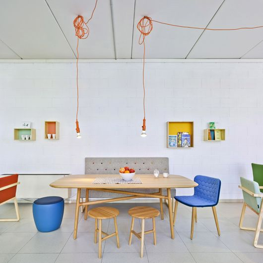 One of the Sancal factory's mini showroom areas - showing the brands penchant for colour. The 'Tea' chair by Estudihac, 'Nudo' table and 'Nudo' timber stools by Juan Ibañez are shown with the blue upholstered 'Chat' stool by Nadadora and 'Menu' sofa by Rafa Garcia at the back. The chairs on the edges of  frame are 'Midori' by Ebuala.
