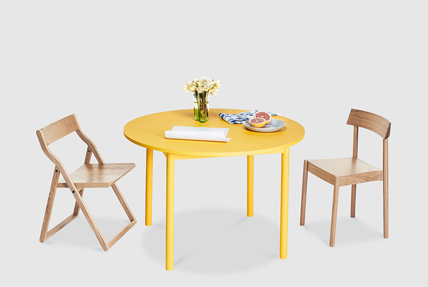 A round version of the 'Time' dining table in a yellow painted finish with the 'Storyteller's' chair (left) and the 'Woodstack' chair (right), both in clear finished oak.