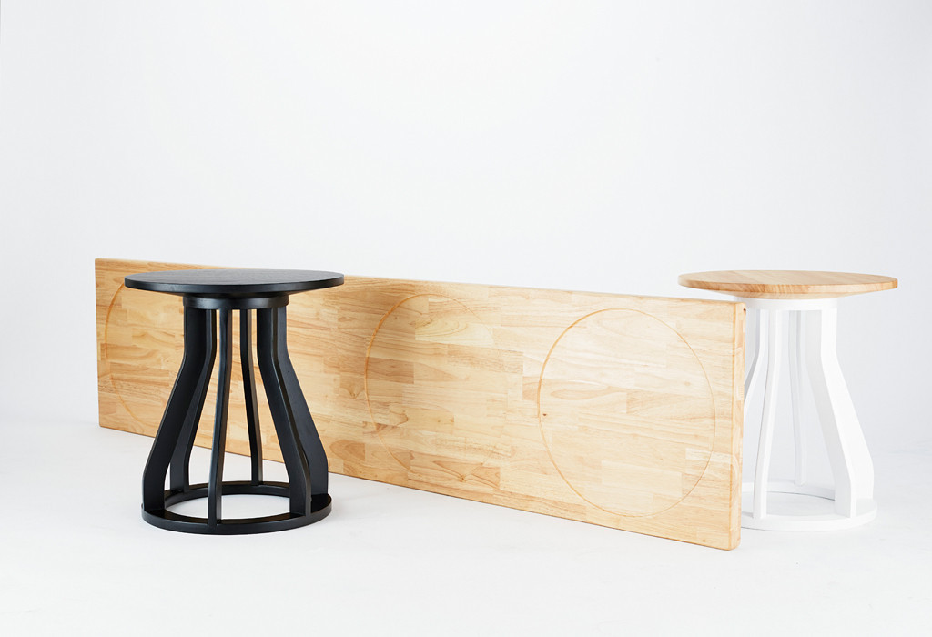 """Jon Goulder's 'Plank' bench uses two """"Spool' stools in combination with a bench element that uses a simple recessed circle to keep the top in place."""