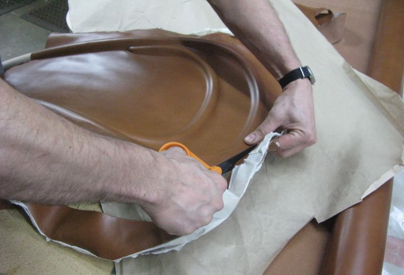 Cutting off excess leather after pressing the leather onto the back framework.