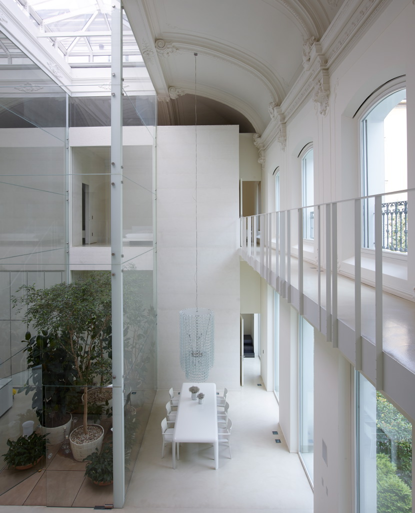 Looking down from the mezzanine to the dining area and glass atrium. The walkway joins the bedroomat the front to a master bedroom at theback of the building.
